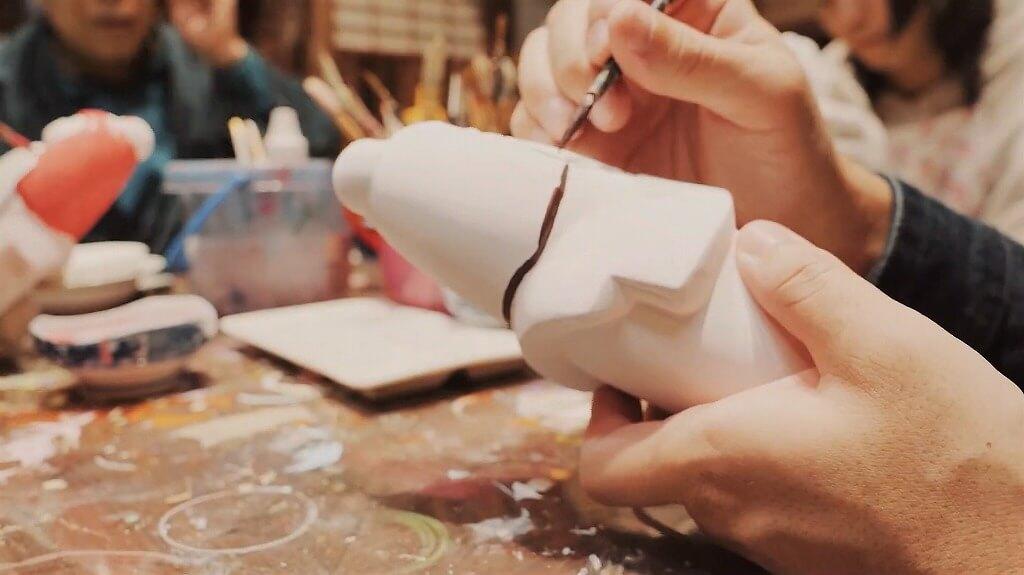 石膏でできた白い博多人形に色を塗る
