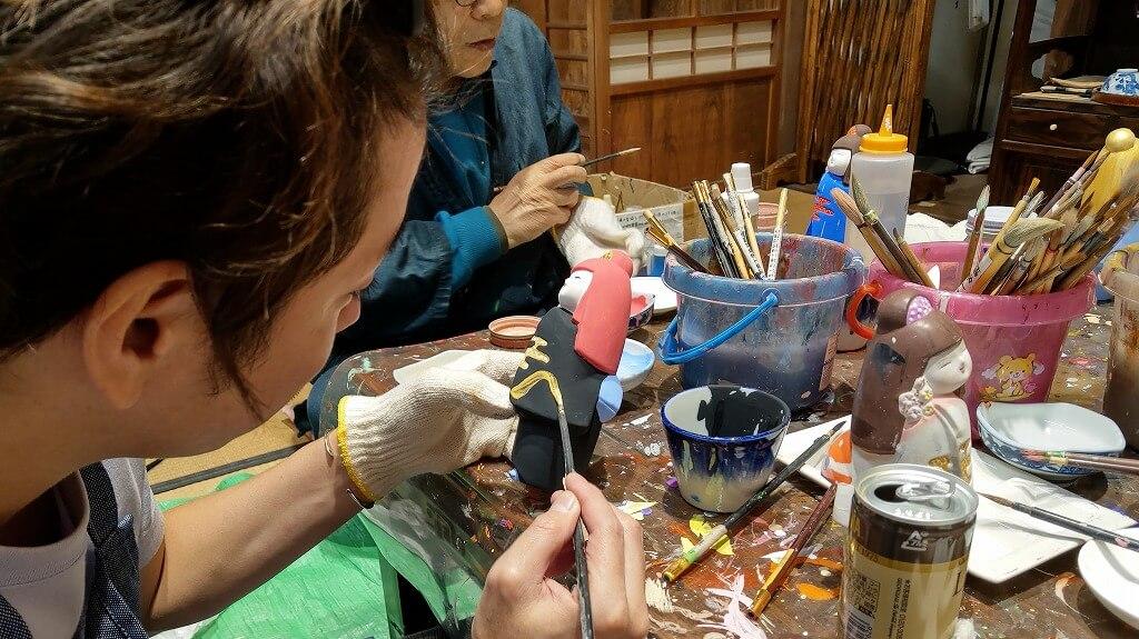 黒い着物の博多人形に金色の塗料で模様を追加していく