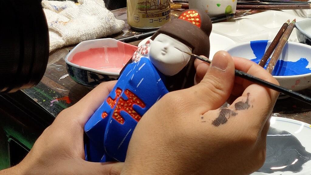細筆で博多人形の目に色塗り