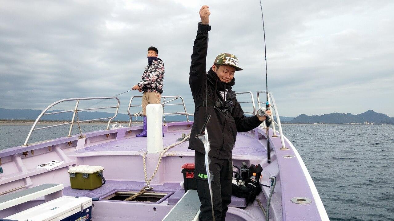タチウオを釣り上げた笑顔の男性