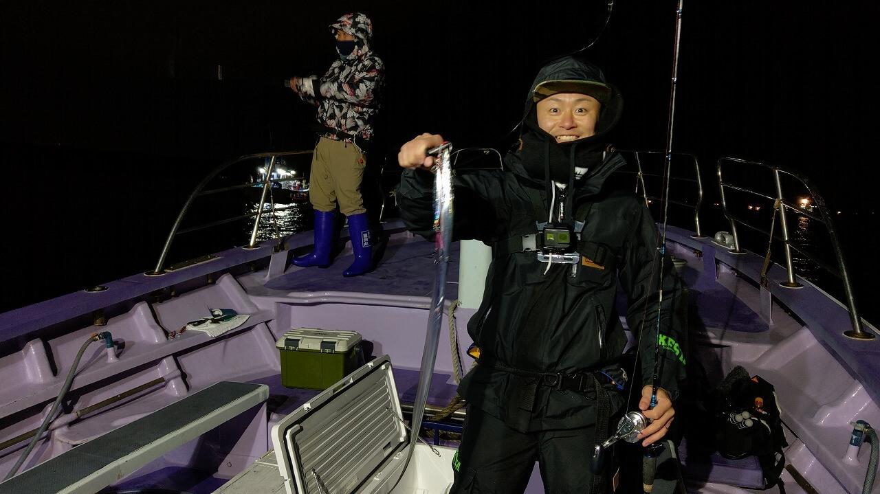 夜の駿河湾でタチウオを釣り上げて笑顔の男性