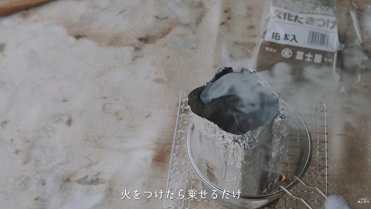 火をつけた着火剤の上に炭をのせる